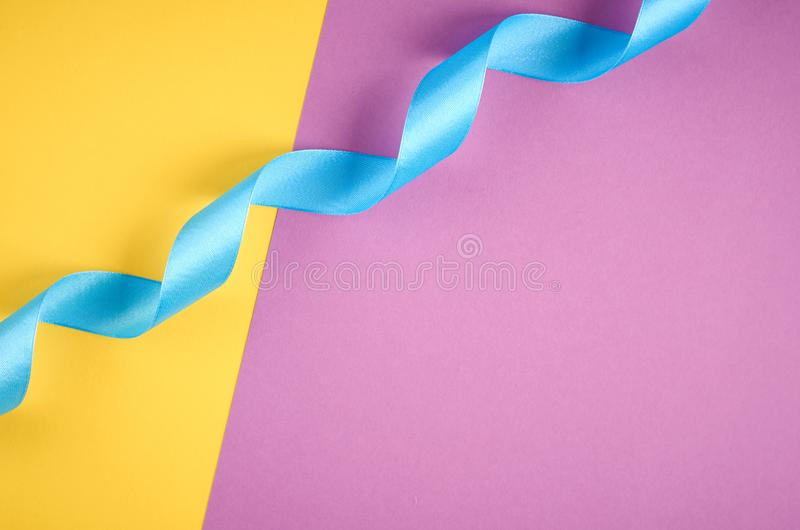Blue ribbon on purple and yellow background composition, flat lay. And top view photo decoration celebration holiday design christmas gift card decorative bow stock image