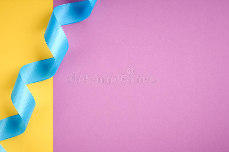 Blue ribbon on purple and yellow background composition, flat lay. And top view photo, decoration, celebration, holiday, design, christmas, gift, card royalty free stock photography