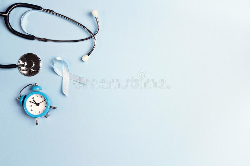Blue ribbon with stethoscope and alarm clock on a blue background. stock photo