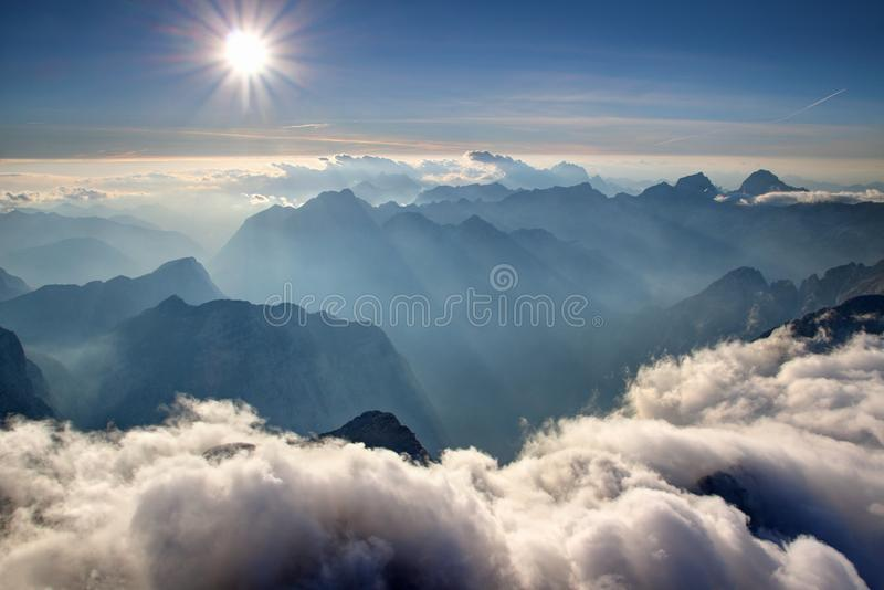 Blue ridges, hazy valleys and white clouds Julian Alps Slovenia. View from Triglav summit with blue ridges of Julijske Alpe range in sunshine, white low heap royalty free stock image