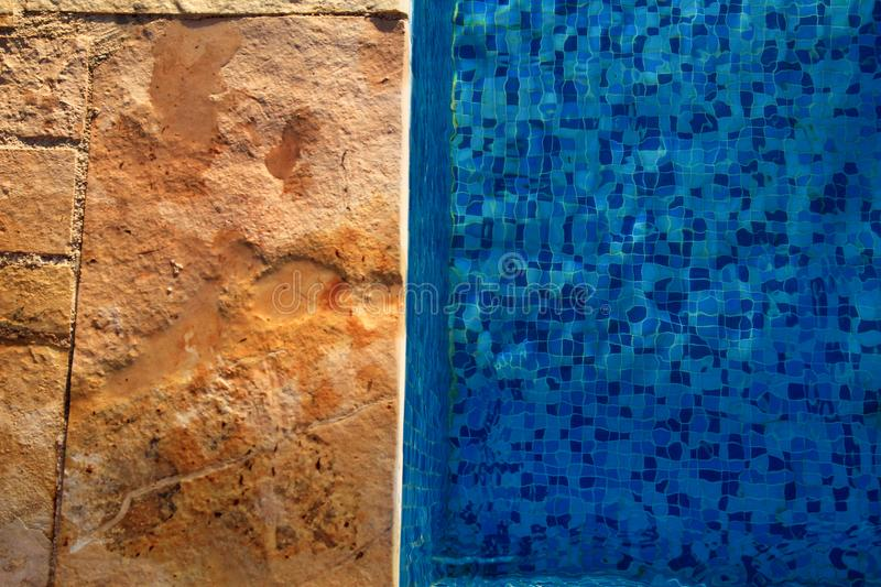 Blue ripped water in swimming pool in tropical resort with edge of pavement. Part of Swimming pool bottom background. stock photo