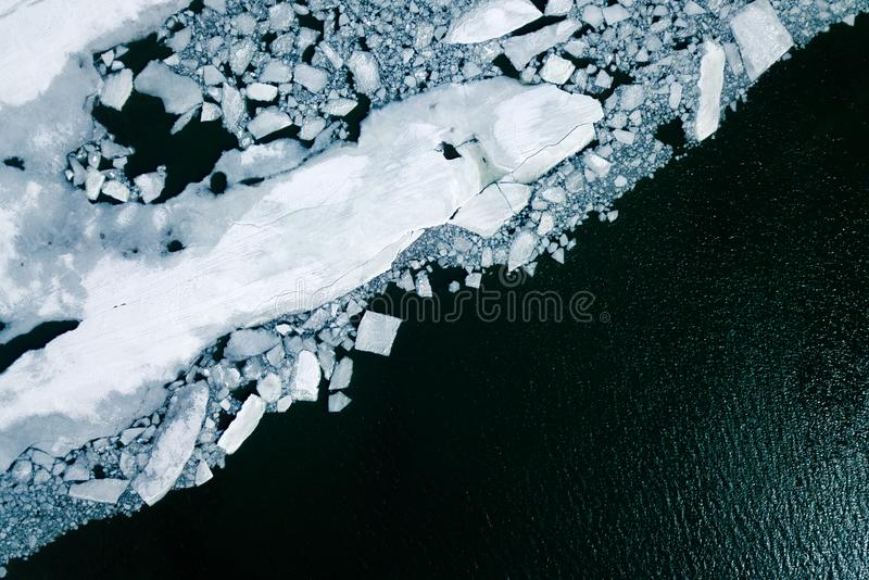 Ice drift with quadrocopter. A blue river, covered with smoothness and cracked ice, is a top view. Ice drift with quadrocopter royalty free stock image
