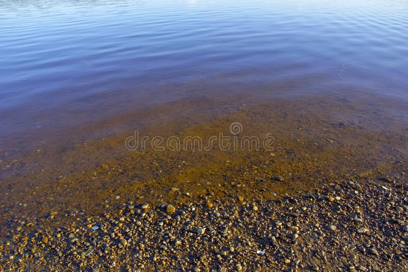 Blue river water and small rocks on the shore royalty free stock image