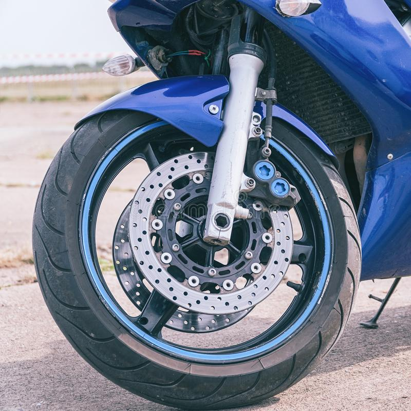 Blue road bike front wheel with disc brake. Blue road bike front wheel with front disc brake royalty free stock images