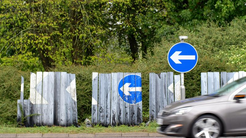 Blue road traffic direction arrow signs on british roundabout on rainy day with cars passing stock photos