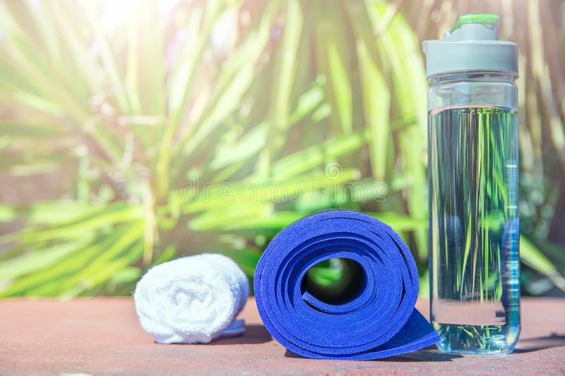 Blue Rolled Yoga Mat Bottle with Water White Towel on Greenery Palm Tree Nature Background. Bright Midday Sunlight. Relaxation stock photo