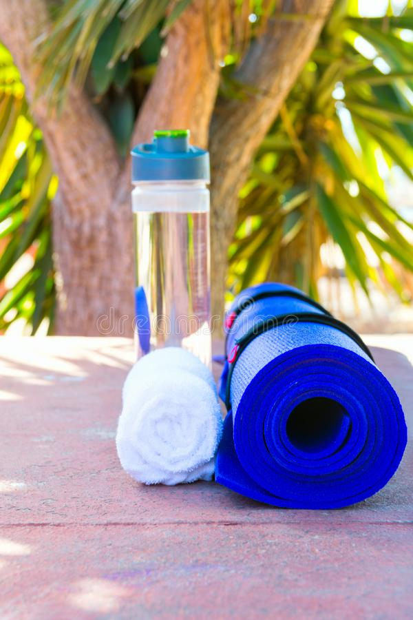 Blue Rolled Yoga Mat Bottle with Water White Towel on Greenery Palm Tree Nature Background. Sunlight. Relaxation Summer Meditation stock photo