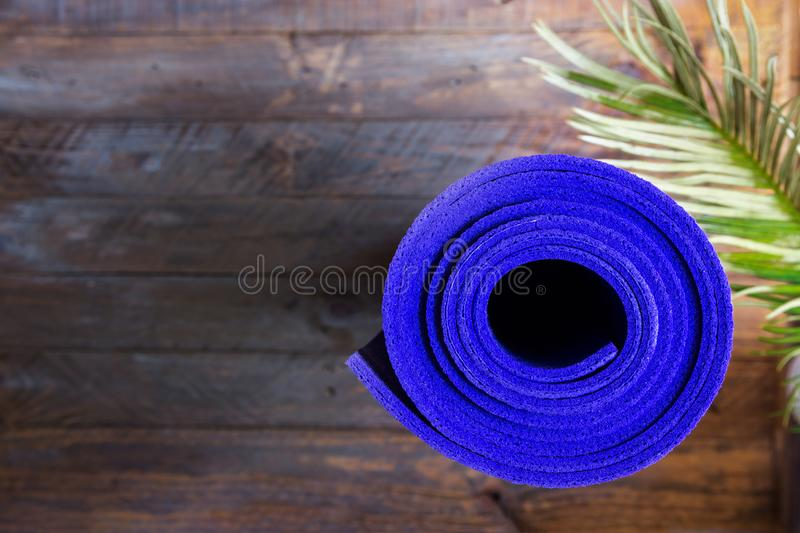 Blue rolled yoga mat lying on wooden background with green palm leaf. Fitness harmony meditation workout retreat concept royalty free stock images