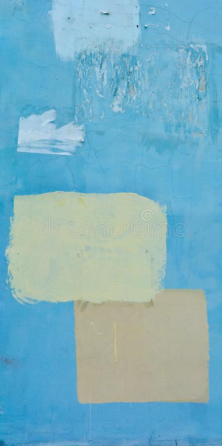 Blue rough concrete wall with a cracks and a painted yellow and orange squares royalty free stock images