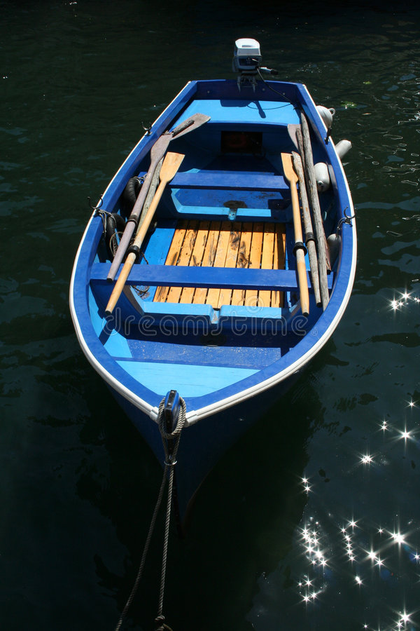 Blue row boat. A blue row boat in the water stock images