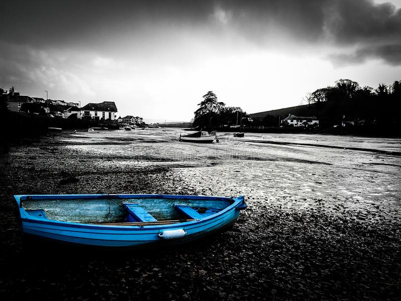 A row boat in Kingsbridge, United Kingdom. A blue row boat on the banks of the Kingsbirdge Estuary, Devon, United Kingdom royalty free stock photos
