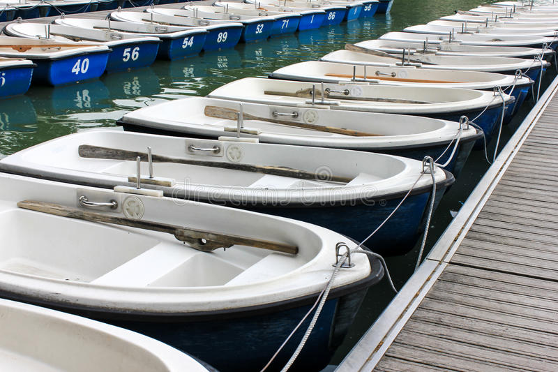 Blue row boats. With paddles in a lake stock images
