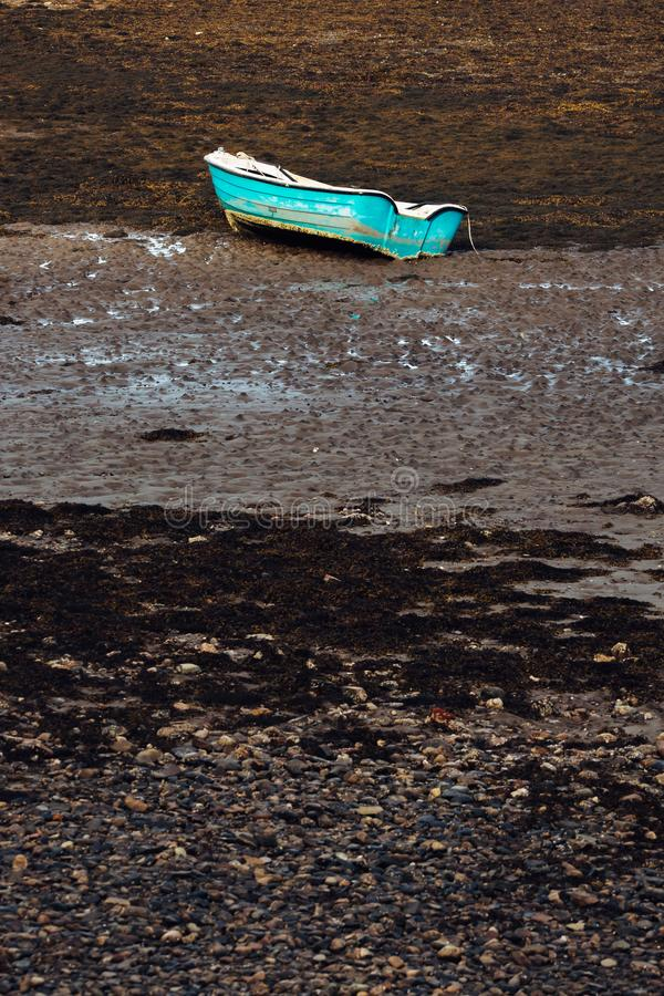 A blue rowing boat stranded on the seabed with the tide out for royalty free stock image