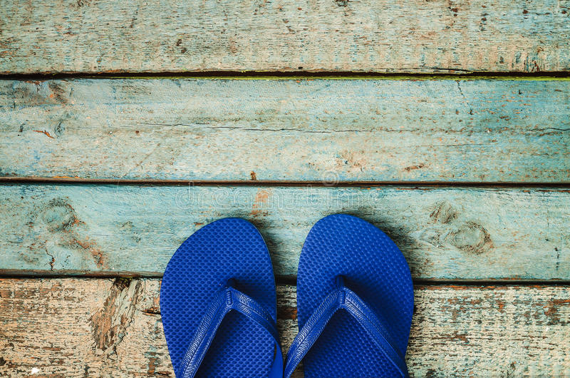 Blue rubber flip flops on a wooden background stock image
