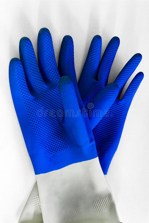 Blue rubber protective gloves on the white background for different surfaces in room, bathroom, kitchen. Early spring or regular royalty free stock image