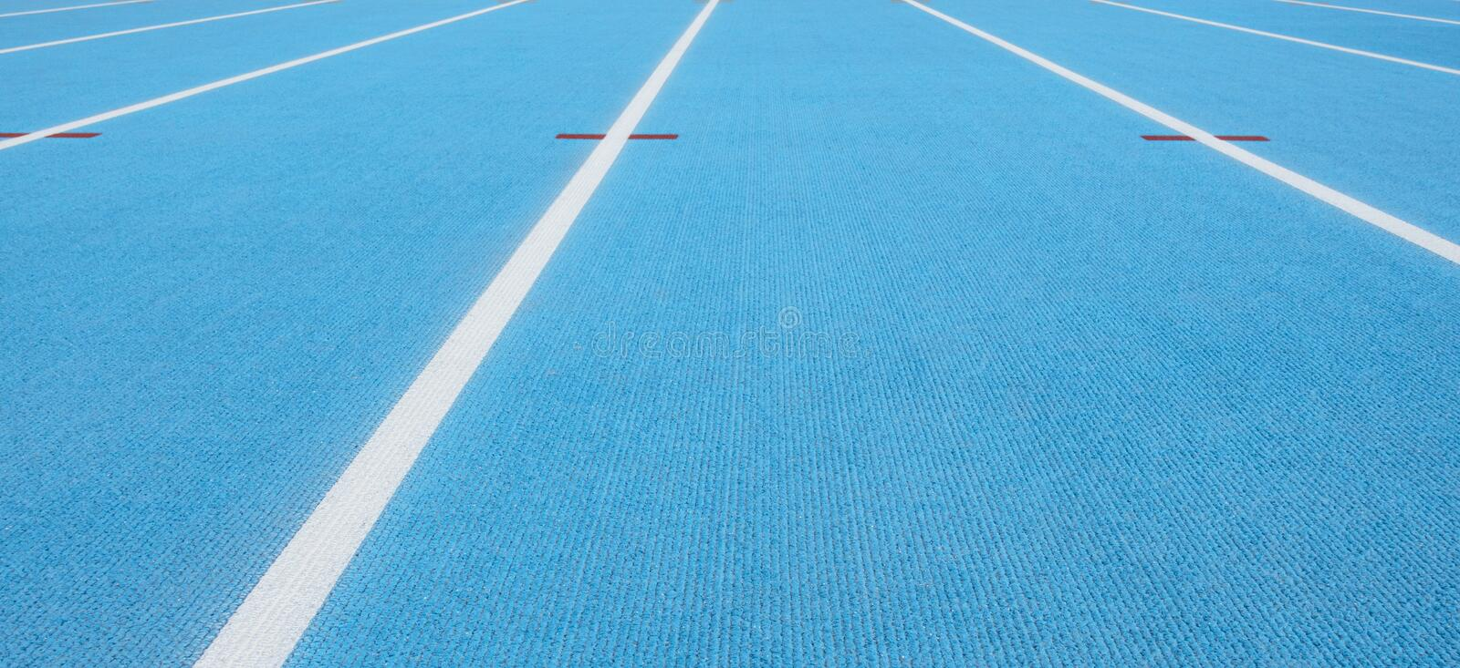 Blue running track with white lines and red mark in sport stadium. Top view. Blue running track with white lines and red mark in sport stadium stock photo