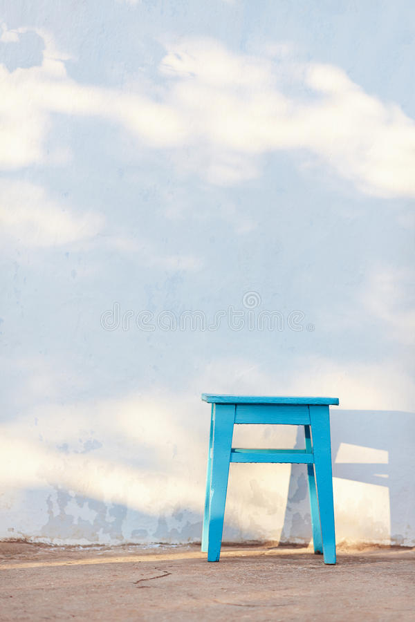 A blue rural stool on white wall background. Blue rural stool on white wall background royalty free stock photo