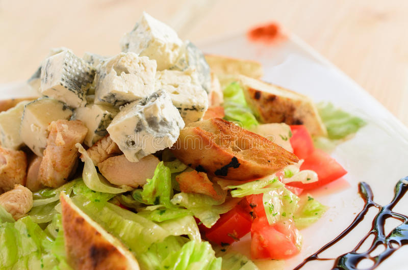 Blue salad with chicken meat, blue cheese, iceberg, lettuce, tomato, bread and dressing royalty free stock image