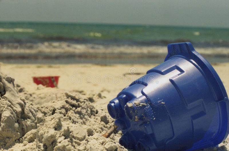 Blue Sand Toy on Beach. With red bucket in back royalty free stock photography