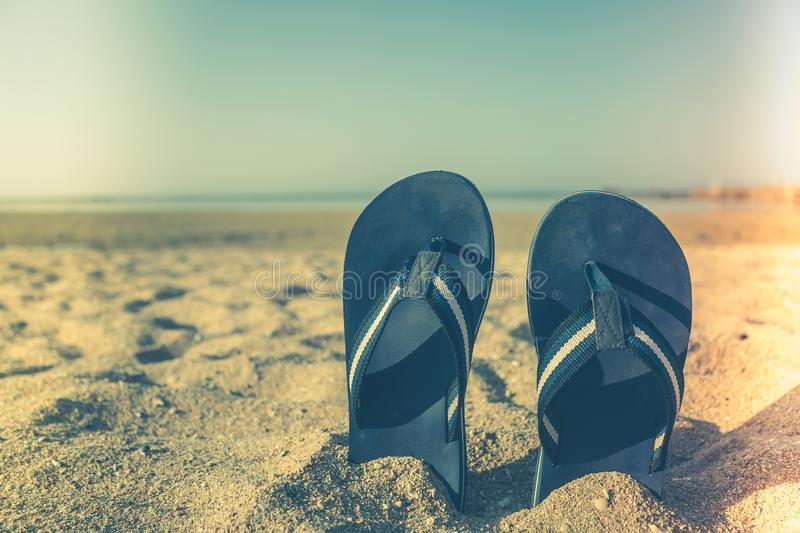 Blue sandal flip flop on yellow sand. Summer fun time and access royalty free stock photos