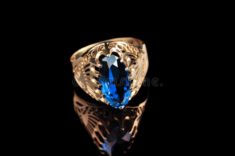 Blue sapphire. Vintage golden ring with blue sapphire stock photography