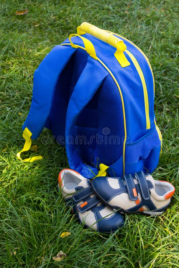 Blue school backpack with sneakers,to prepare for the school year, a backpack on the grass with shoes. To prepare for the school year, a backpack on the grass royalty free stock image