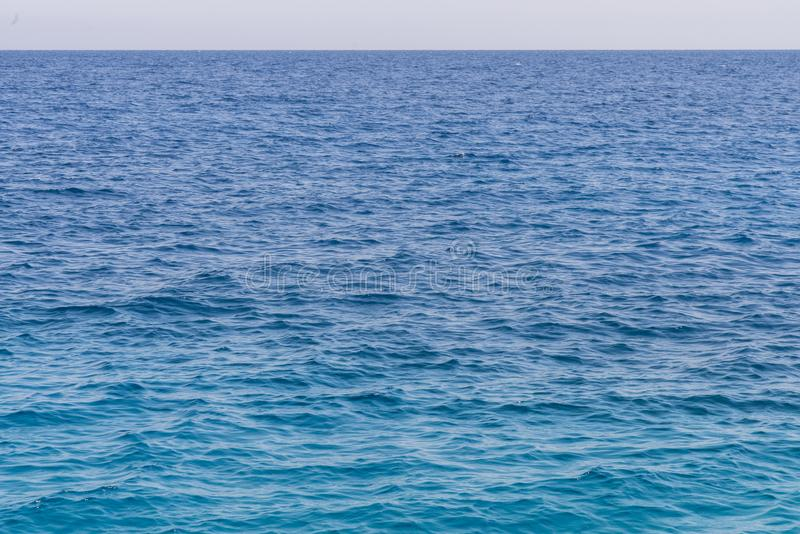 Blue sea background. Beautiful sky and blue ocean or sea. Blue sea surface with waves stock photos