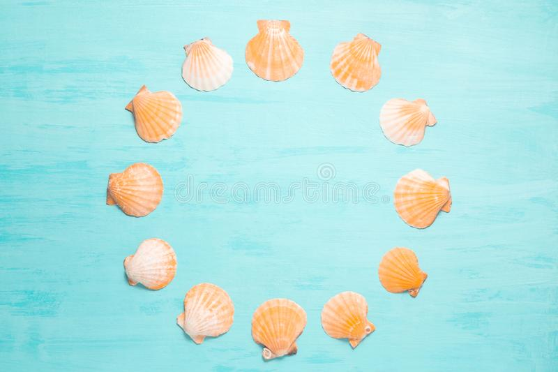 Blue sea background with copy space and round frame made of seashells, summer holiday and vacation concept royalty free stock photography