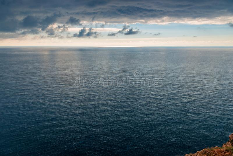 The blue sea and black storm clouds, the elements. Of a beautiful landscape royalty free stock photography