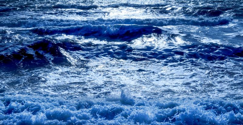 A blue sea glistening white. A dark blue sea with waves swelling the sea has dark shadows where the waves are swelling and the sunlight is glistening white on stock images