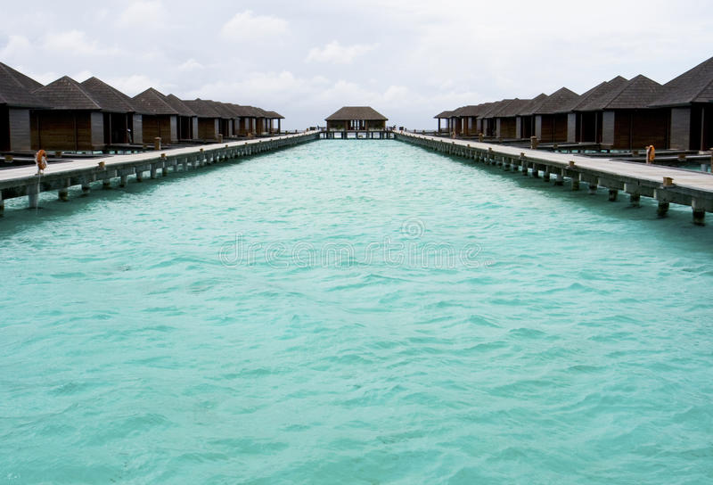 Blue sea and holiday chalets. Holiday chalets lining a blue lagoon, Paradise Island, Maldives stock photos