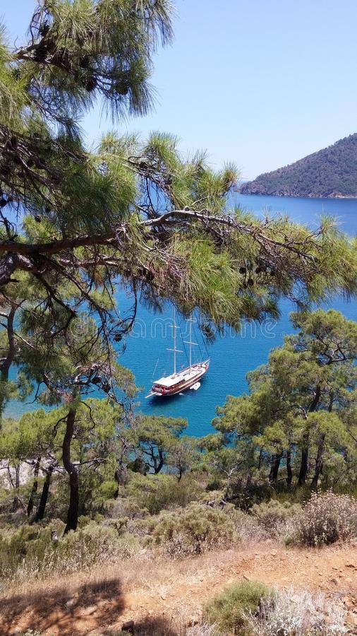Blue sea laguna with yacht and pines trees at foreground. Adrasan Beach Turkey stock photo