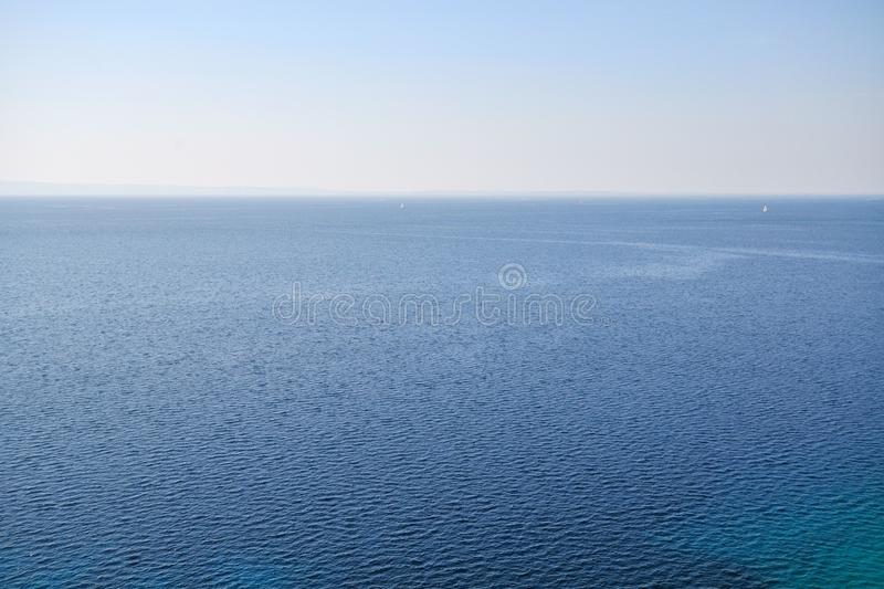 Blue sea landscape. Deep blue sea landscape with two boats on the horizon in summer time stock images
