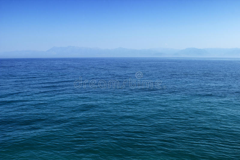 Blue sea or ocean water surface with horizon and sky stock images
