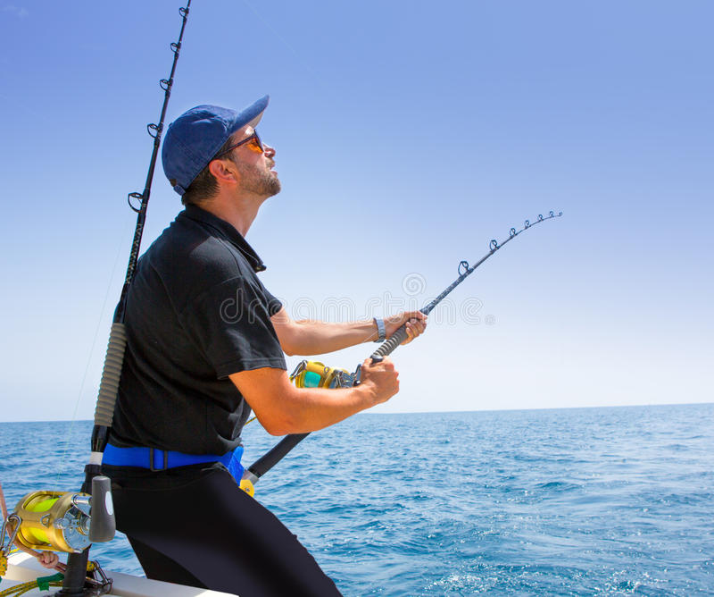 Blue sea offshore fishing boat with fisherman. Holding rod in action royalty free stock photo