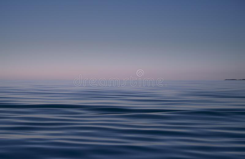 Blue sea and pink sky background. Waves shot at long exposure royalty free stock images