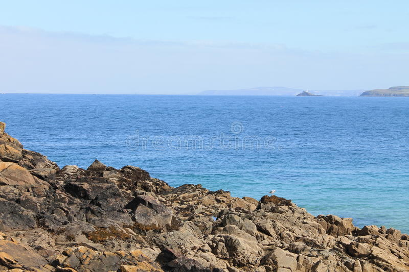 Blue sea and rocky coast and distant lands at Cornwall, England stock photo