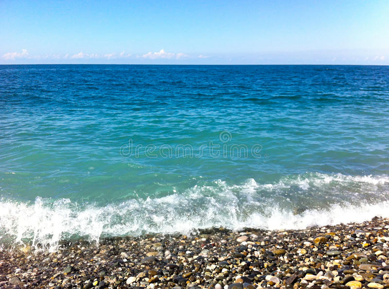 Blue sea. S and shore with pebbles royalty free stock images