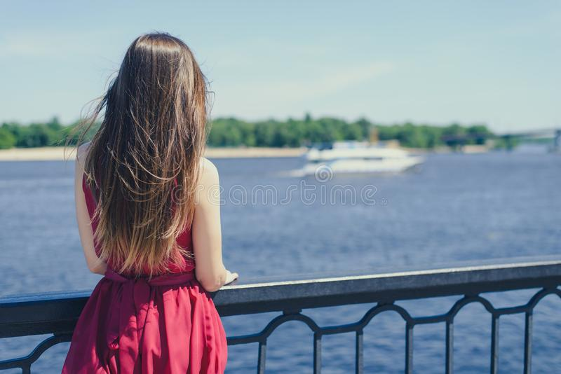 Blue sea sky life sails-man cry day dream sad dreamy lady in red dress concept. Rear back behind view photo portrait of beautiful stock image