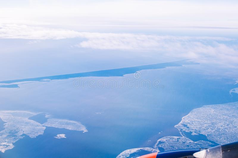 Blue sea and sky from the window of airplane. Spit in the sea stock photo
