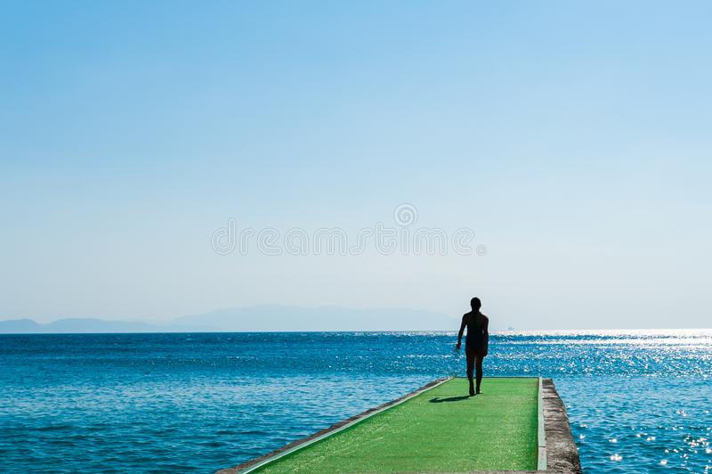 Man goes to the green pier to dive stock photos