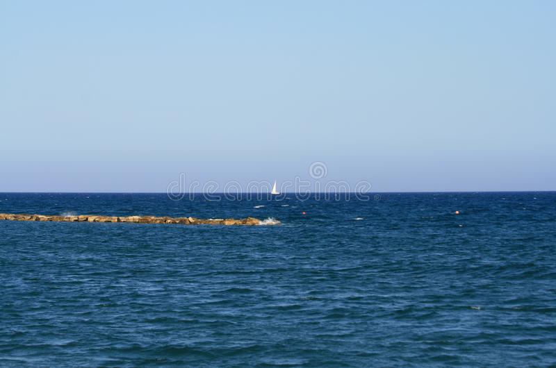 Blue sea with white sail on horizon royalty free stock photos