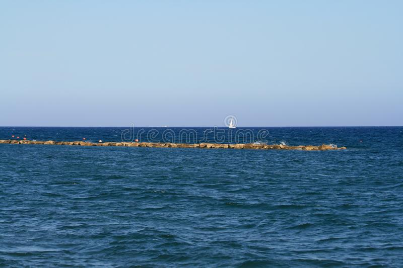 Blue sea with white sail on horizon. Panoramic view of the dark blue sea with a white sail boat on the horizon and the light blue sky from Limassol seafront stock photo