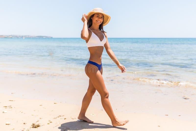 Blue sea, white sand paradise. Full length portrait of modern latin woman in bikini and beach straw hat on the seashore walking. Blue sea, white sand paradise royalty free stock image