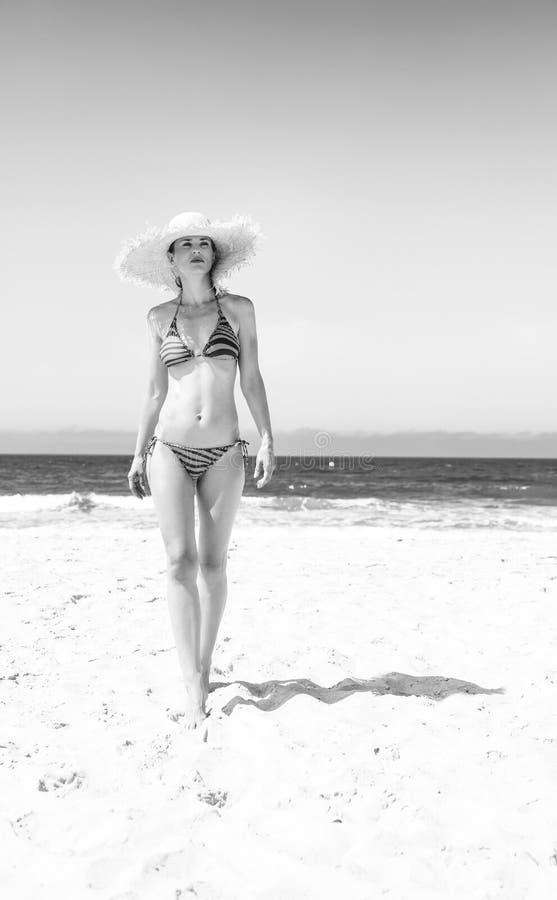 Modern woman in bikini and beach straw hat on seashore walking. Blue sea, white sand paradise. Full length portrait of modern woman in bikini and beach straw hat royalty free stock photography