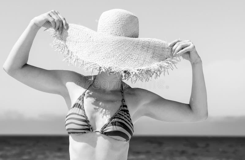 Modern woman on seashore hiding behind beach straw hat. Blue sea, white sand paradise. modern woman in bikini on the seashore hiding behind beach straw hat stock image