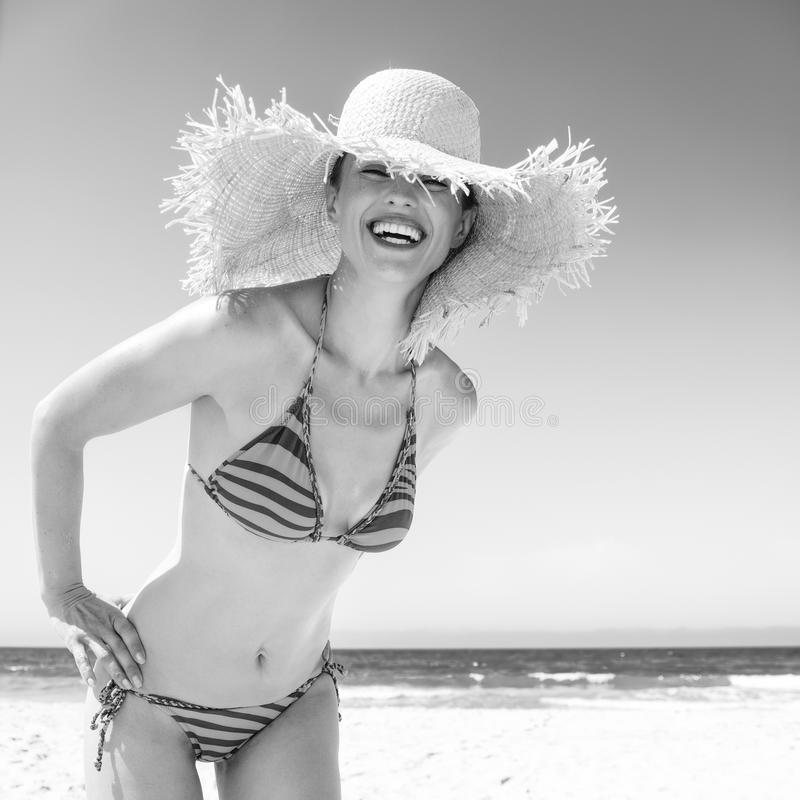 Smiling modern woman in bikini and beach straw hat on seacoast. Blue sea, white sand paradise. smiling modern woman in bikini and beach straw hat on the seacoast royalty free stock photography