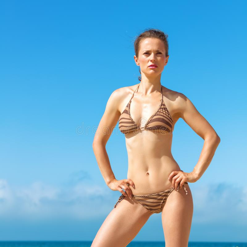 Young woman in bikini on beach looking into distance stock photography