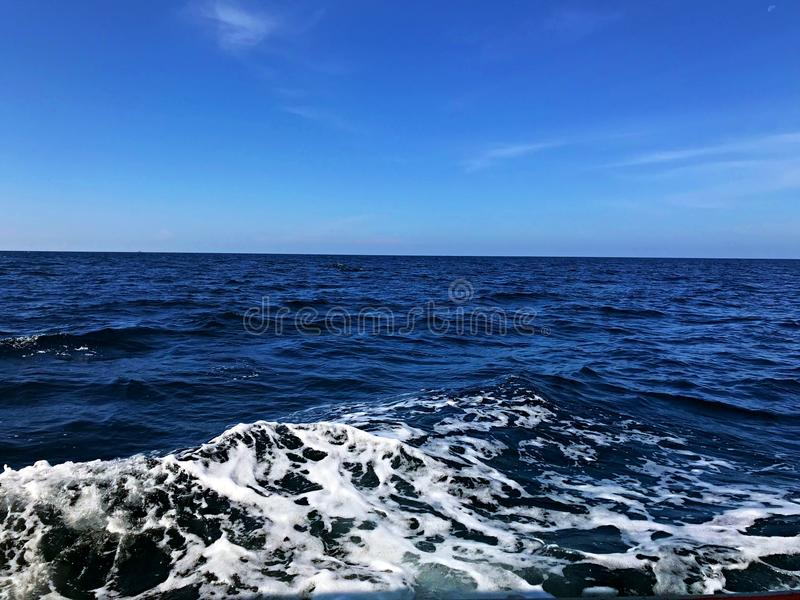 Blue sea with white wave and horizon. Blue sea and the wave with blue sky and horizon royalty free stock photo