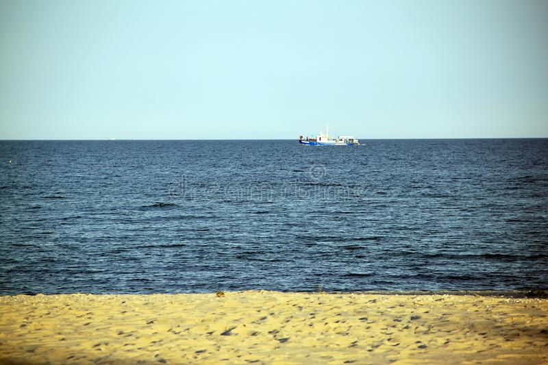 Blue sea, yellow sand, white ship stock photography
